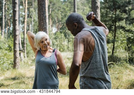 Senior Woman Smiling While Exercising With African American Husband In Forest.