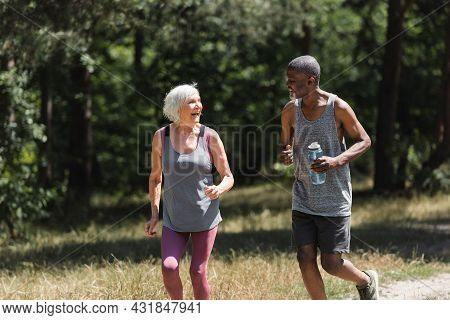 Cheerful Multiethnic Couple With Bottle Of Water Running In Forest.