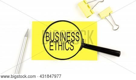 Business Ethics Text On The Sticker Through Magnifier. View From Above. Business