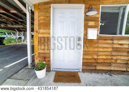 White Front Door Decorated With Flowers On A Pot And Doormat With Welcome Sign