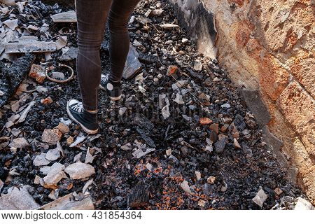 Human Legs Wearing Jeans And Sneakers Standing In House Destroyed With The Fire. Damaged Walls, Burn