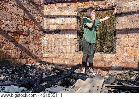 Young Woman Calls By Mobile Phone, Standing In House Destroyed With Fire. Damaged Window, Walls And