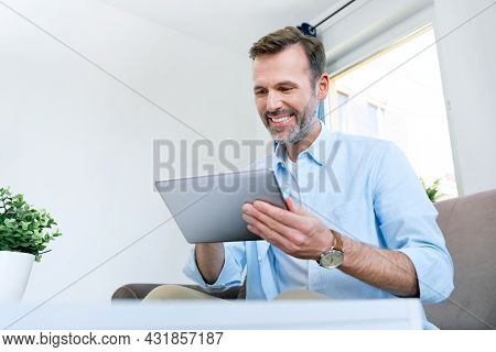 Handsome Businessman Working From Home. Using App On Tablet To Telecommuting Or Sales Reporting