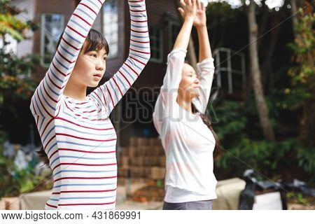 Asian mother and daughter exercising outdoors and practicing tai chi. family fitness time in garden.