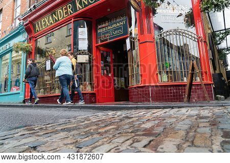 Ennis Ireland - August 12 2017; People Blurred In Motion Walking Past Exterior Facade Styl;e Of Famo