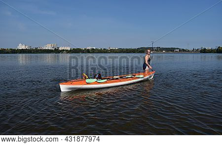 A Young Woman Overcomes Shallow Water By Dragging The Kayak.