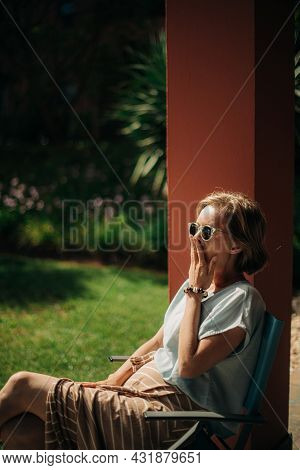 Portrait Of Woman Resting On Chair Outdoors. Mid Adult Lady Wearing Sunglasses Sitting On Terrace An