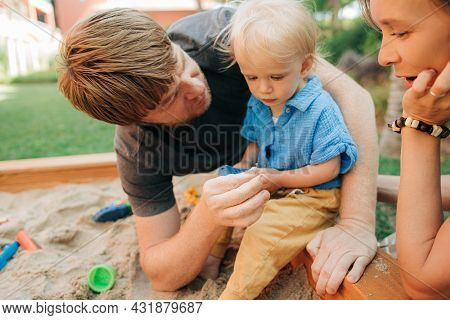 Mid Adult Man And Woman Playing With Child In Sandpit. Man Talking To Serious Little Girl Sitting In
