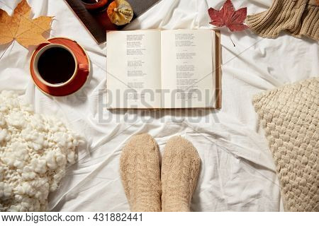 season and leisure concept - book, cup of coffee, feet in warm socks and autumn leaves in bed