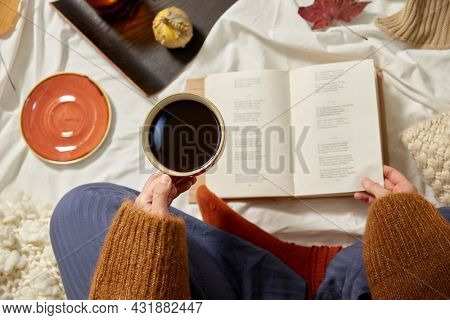 people, season and leisure concept - young woman drinking black coffee and reading book at home in autumn