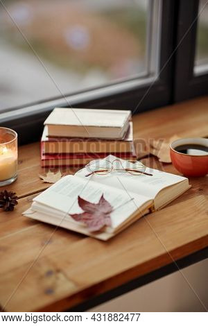 season, leisure and objects concept - open book, cup of coffee, autumn leaves and candle on window sill at home