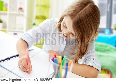 education, art and school concept - smiling student girl with colorful felt-tip pen drawing picture in notebook over home room background