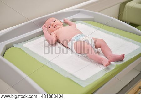 The Baby Infant Boy Lies In A Diaper On The Changing Table In The Clinic. Happy Child Changing Cloth