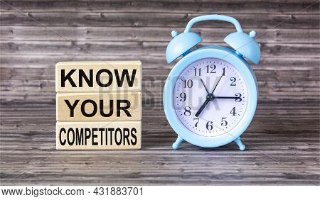 The Text Know Your Competitors Is Written On Wooden Blocks And On A Wooden Background With An Alarm