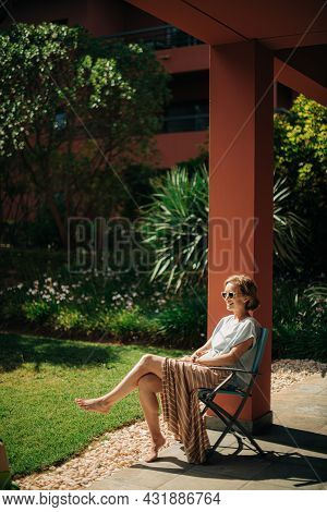 Happy Mid Adult Woman Enjoying Summer Day Outdoors. Lady Wearing Sunglasses Sitting In Chair And Smi
