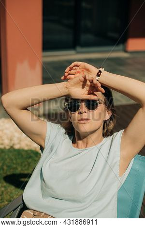 Portrait Of Mid Adult Woman Wearing Sunglasses. Confident Lady Sitting On Chair And Looking At Camer