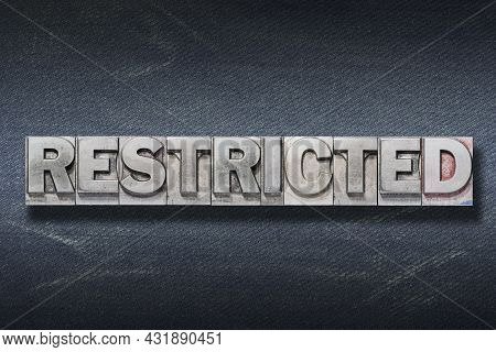 Restricted Word Made From Metallic Letterpress On Dark Jeans Background