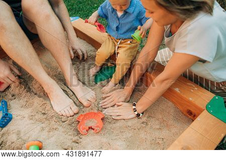 Close-up Of Parents Playing With Child In Sandbox. Mid Adult Woman, Man And Toddler Girl Touching Sa