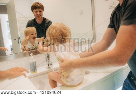 Funny Little Girl And Father Grimacing At Mirror In Bathroom. Man Having Fun With His Child At Home.