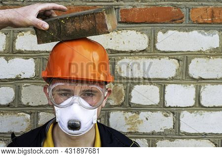 A Construction Worker In A Protective Construction Helmet, A Respirator And Protective Glasses Again