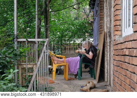 Batumi, Georgia, August, 21, 2021: Older Woman Reading Book On The Porch