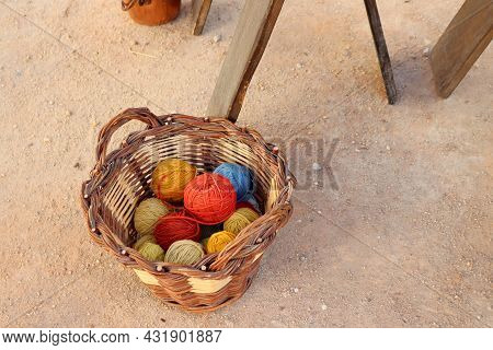 Multi-colored Balls Of Yarn For Knitting.     A Pile Of Woolen Threads In A Wicker Basket .
