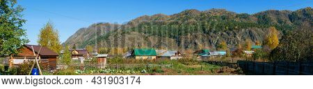 Panoramic View Of Wooden Houses And A Vegetable Garden Against The Background Of The Altai Mountains