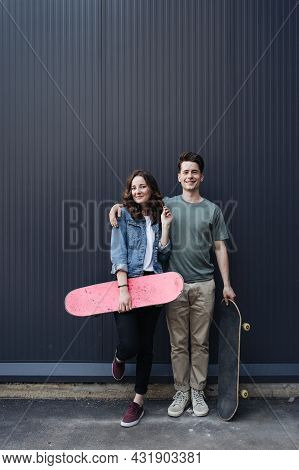 Caucasian Skateboarder Couple Standing Together Prepare Themselves To Surf Skate On Gray Wall. Hands