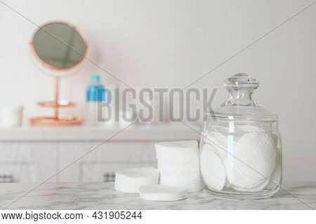 Glass Jar With Cotton Pads For Removing Makeup On White Marble Table In Bathroom