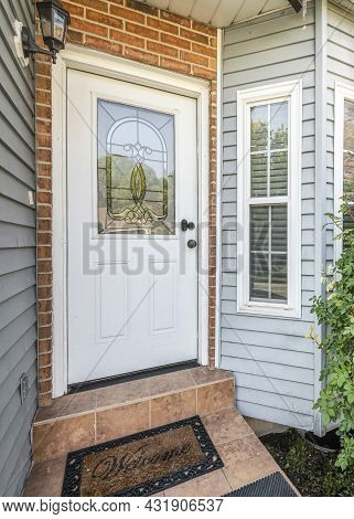 Vertical Front Door Exterior With Bricks And Vinyl Siding Wall