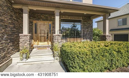 Pano Front Exterior Of A Two Storey House With Stone Brick Walls And Shrubs At The Front