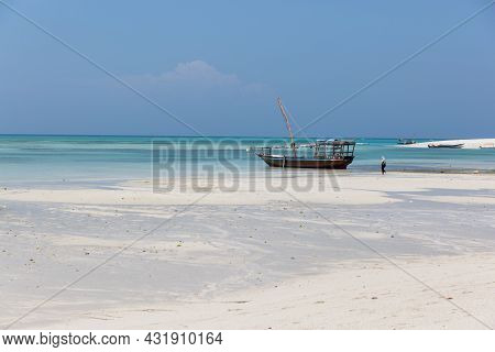 Zanzibar, Tanzania, January 18, 2021: A Fishing Boat Is Moored And Aground At Low Tide Against The B
