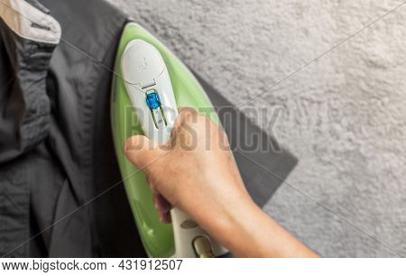 Women Wearing Gray Shirt Ironing Clothes On Ironing Board In Laundry Room At Home. The Concept Of Ca