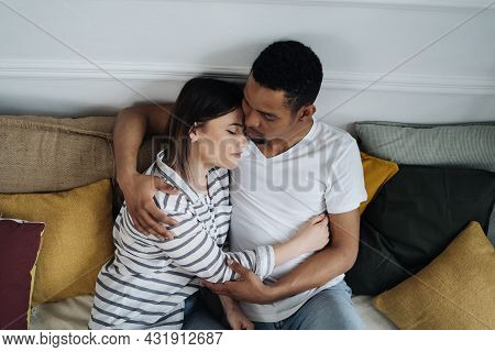 Portrait Of Happy Young African Caucasian Couple Hug Sitting On Couch At Home, Smiling Mixed Race Hu