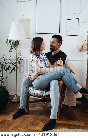 Portrait Of Happy Young African Caucasian Couple Hug Sitting On Armchair At Home, Smiling Mixed Race