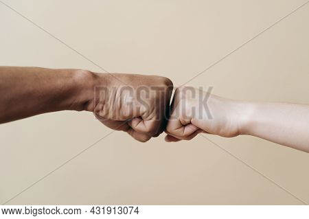 Multiethnic Couple Hands Making Fist Bump. Young Caucasian Woman And African Male Fists Together On