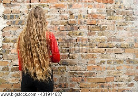 The Woman Stands With Her Back To The Camera. Beautiful Long Curly Hair. Blonde On A Background Of A