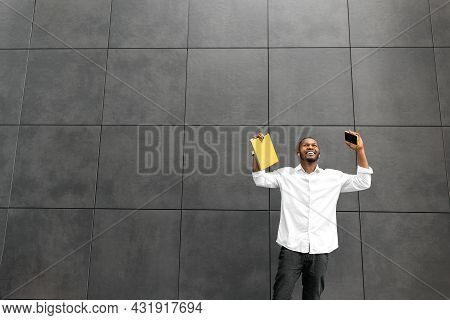 Overjoyed African American Businessman Or Student Looking Up, Excited About Good News. Stylish Male