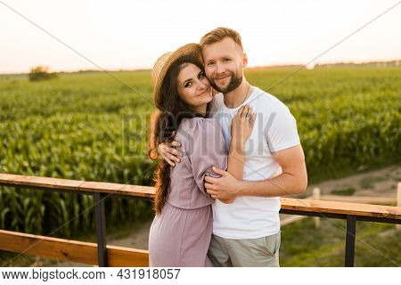 Portrait Of Happy Couple Standing At The Field, Hugging, Enjoying Moments Together. Beautiful Woman
