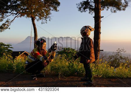 Young And Cute Mom Holding And Using Smartphone Takin Photo Of Her Little Son In The Morning Light D