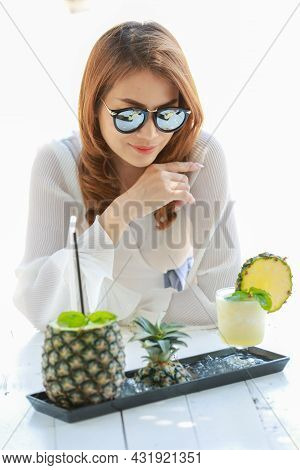 Woman Wearing Sun Protect Sunglasses Sitting And Looking To Set On Pineapple Juice Cocktail Served O