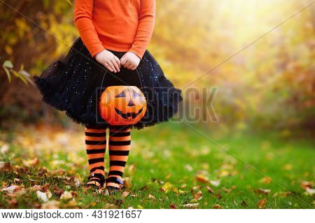Little Girl In Witch Costume Playing In Autumn Park. Child Having Fun At Halloween Trick Or Treat. K