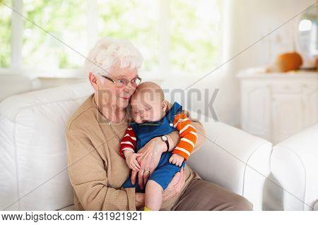 Grandmother Holding Newborn Baby. Family Reunion. Senior Woman With Little Child. Grandma Seeing Gra