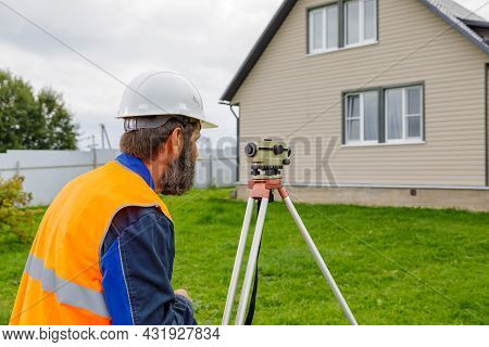 A Male Engineer Works With The Optical Level On Site. A Builder In A Helmet Looks Into An Optical De
