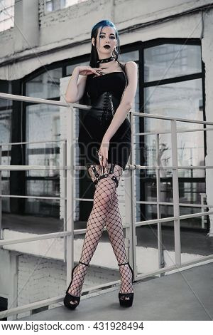 Indoor Portrait Of The Sexy Goth (informal) Girl Dressed In Black Dress, Corset And Pantyhose. Dark
