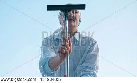 Woman Washes The Window With A Rag Then Pulls Off The Water With A Scraper.