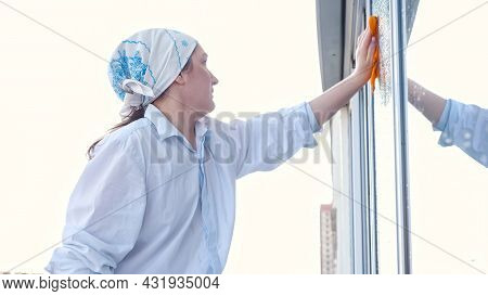 Side View Of A Woman In A Scarf Washes The Window With A Rag.