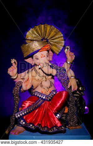 Lord Ganesha, Hindu God Ganesh On Black Background With A Purple Light And Smoke