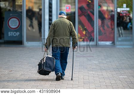 Elderly Man With Cane Walking Down The Street, Rear View, Concept For Disability, Limping