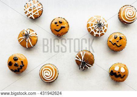 Many Halloween Decorated Cupcakes Scattered About Against A Light Background.